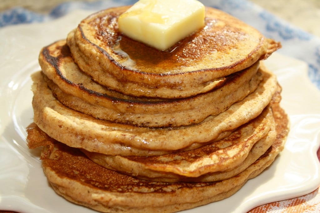 Close up picture of a large stack of pumpkin pancakes on a white plate with a pat of butter on top.