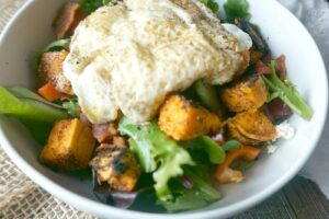 "Sweet Potato Breakfast Salad from A ""Mind"" Full Mom. Seasoned, roasted sweet potatoes are tossed with a mixed greens and sharp feta cheese. Finished off perfectly with fried egg."