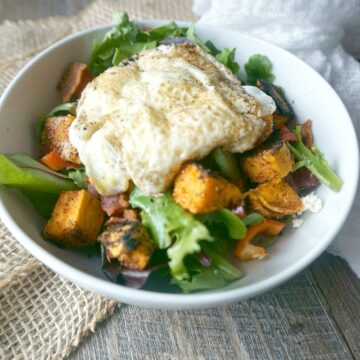 """Sweet Potato Breakfast Salad from A """"Mind"""" Full Mom. Seasoned, roasted sweet potatoes are tossed with a mixed greens and sharp feta cheese. Finished off perfectly with fried egg."""