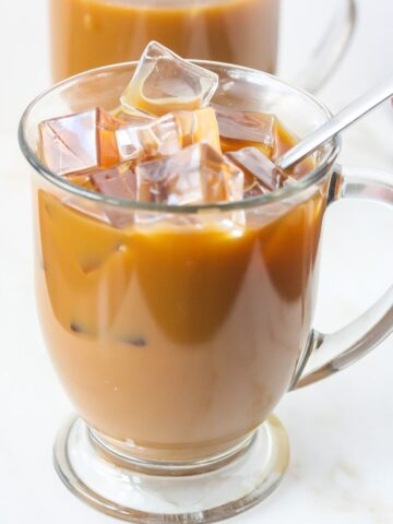 Close up of Iced Mocha Latte with ice cubes in a clear mug.