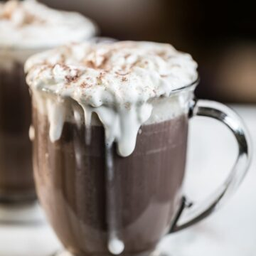 Close up of bulletproof hot chocolate in a clear glass with whipping cream dripping down the front.