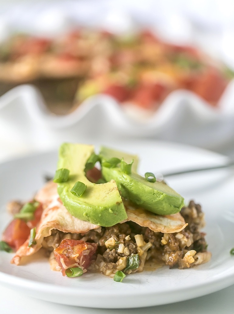 Close up of a piece of tortilla taco pie on a white plate with sliced avocado on top.