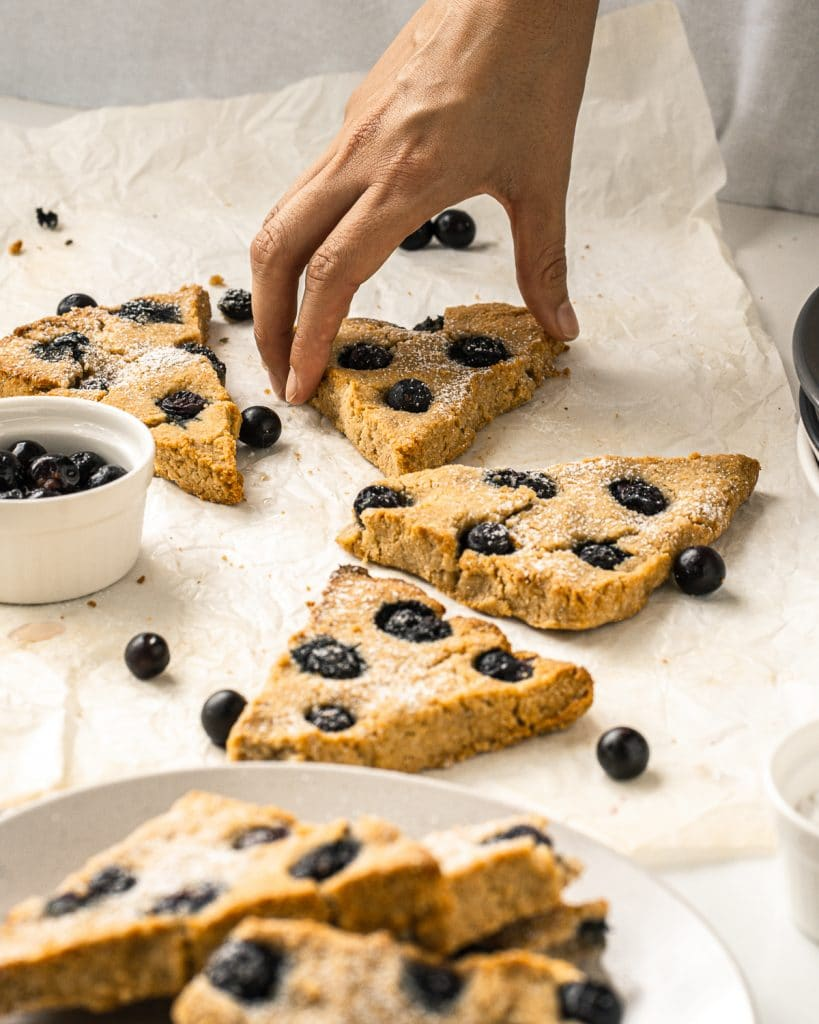 Scones laying on parchment paper with a hand grabbing one scone and some on a white plate up front.