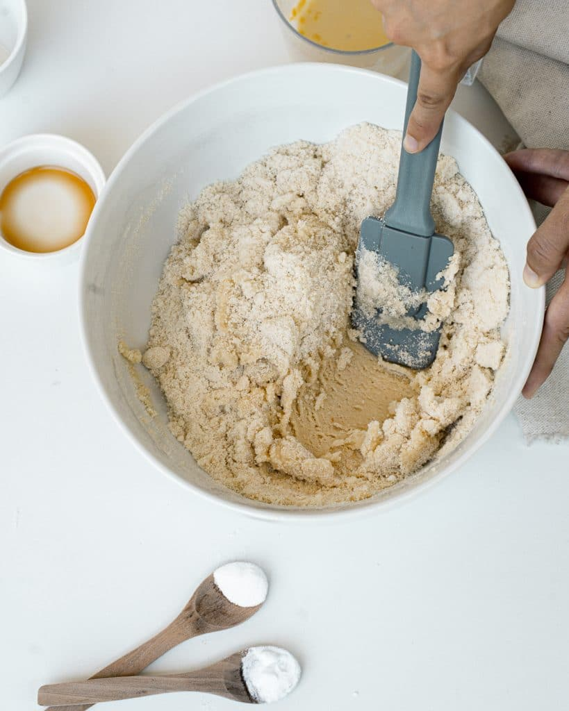 Large bowl with all ingredients with grey spatula mixing together.