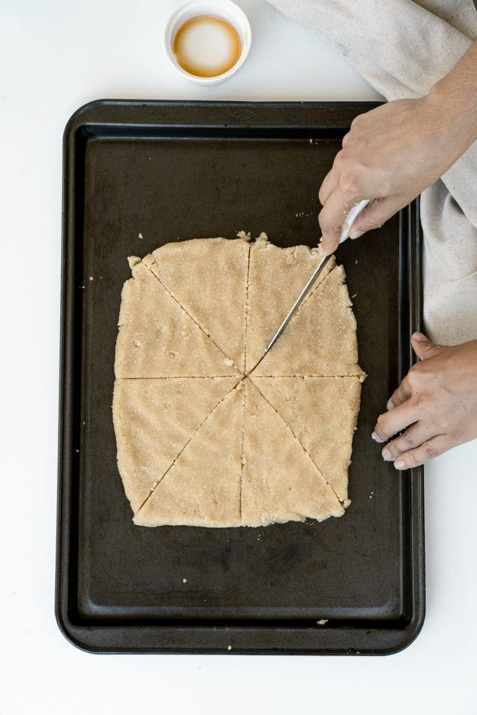 Dough on baking sheet while being cut into 8 pieces.