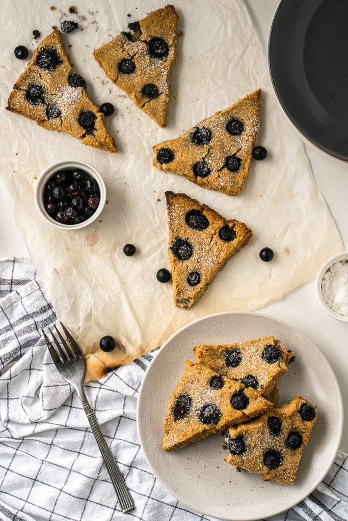 Scones spread out on a white cloth with a small white jar of blueberries and a fork in the bottom left.