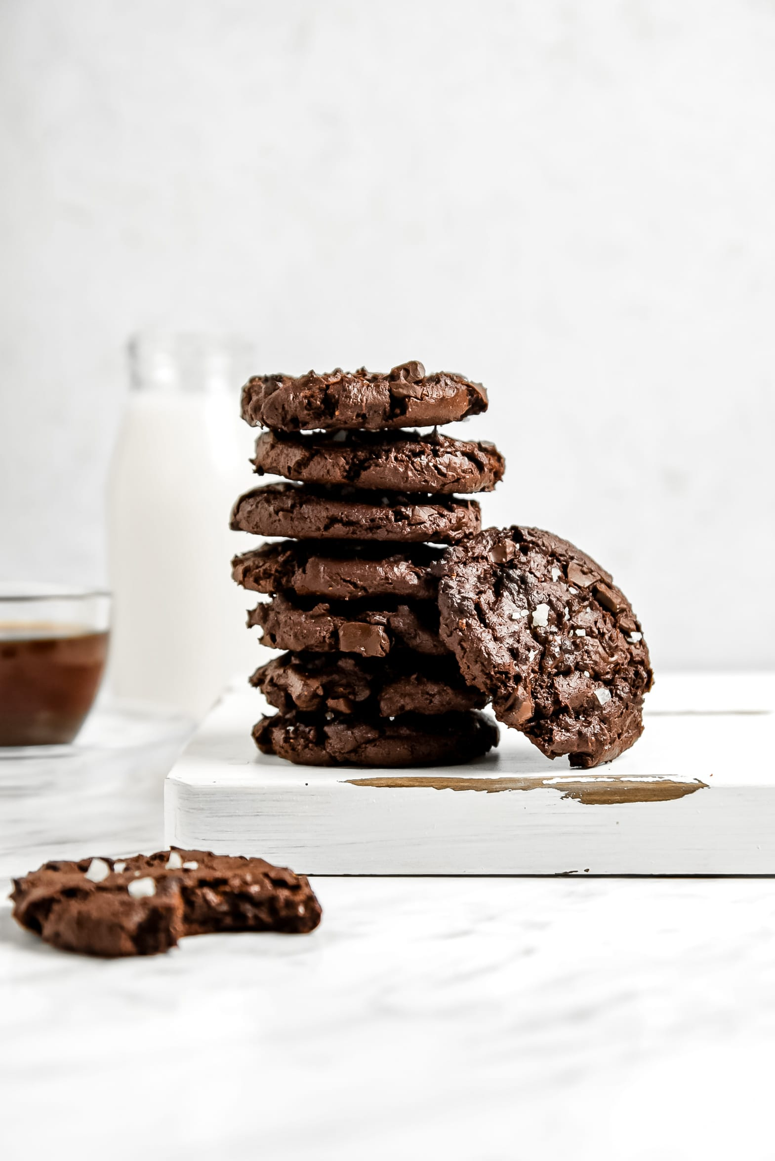 Vertical picture of a stack of brownie cookies on a white plate with one cookie leaning on the stack and a bitten brownie cookie in the front.