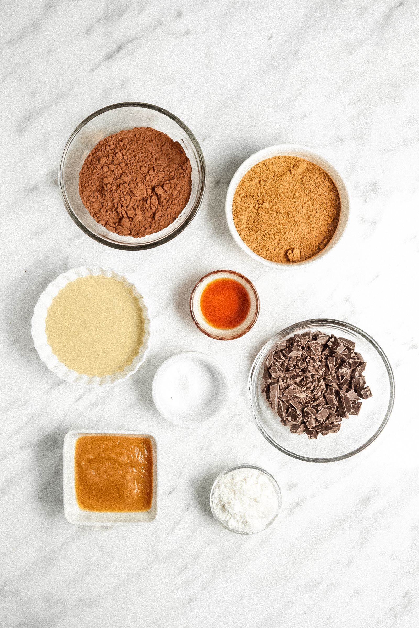 Picture of all 8 ingredients of the brownie cookies in small bowls on a marble counter.