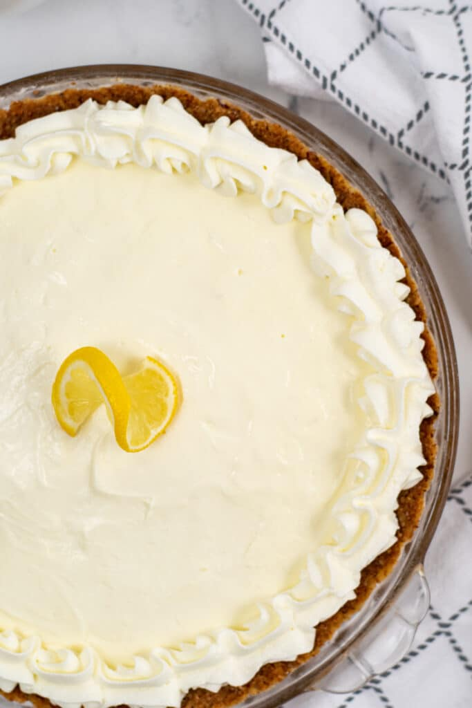 Close up picture of lemon pie with whipped topping on top and lemon slices in the middle.