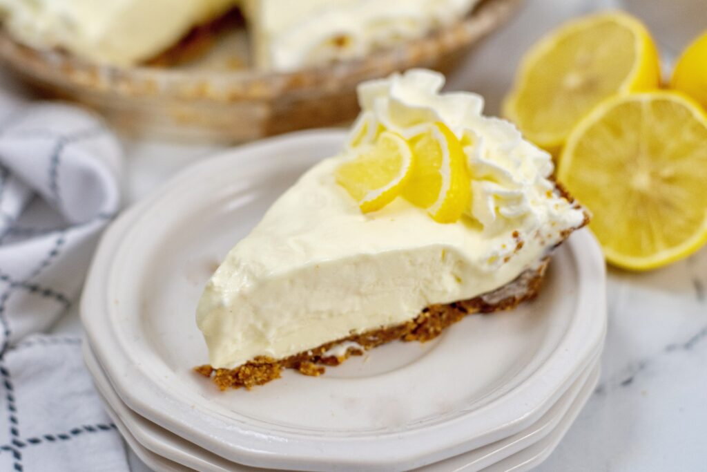 Horizontal picture of a slice of lemon pie on stacked white plates and half a lemon in the upper right corner.