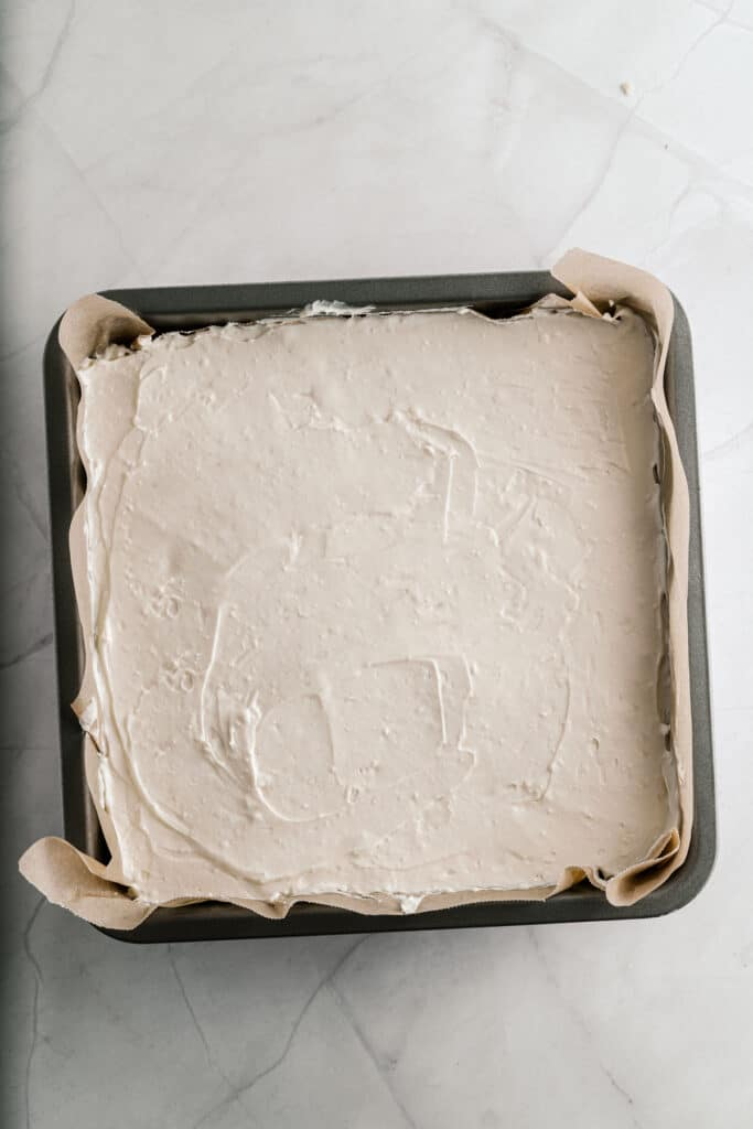 Overhead picture of cheesecake layer in a baking pan.