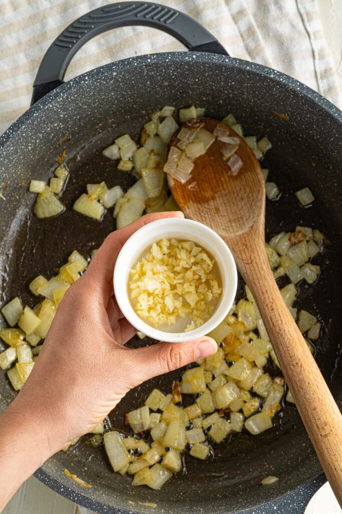 Close up picture of onion in a pan cooking with a wooden spoon in it.