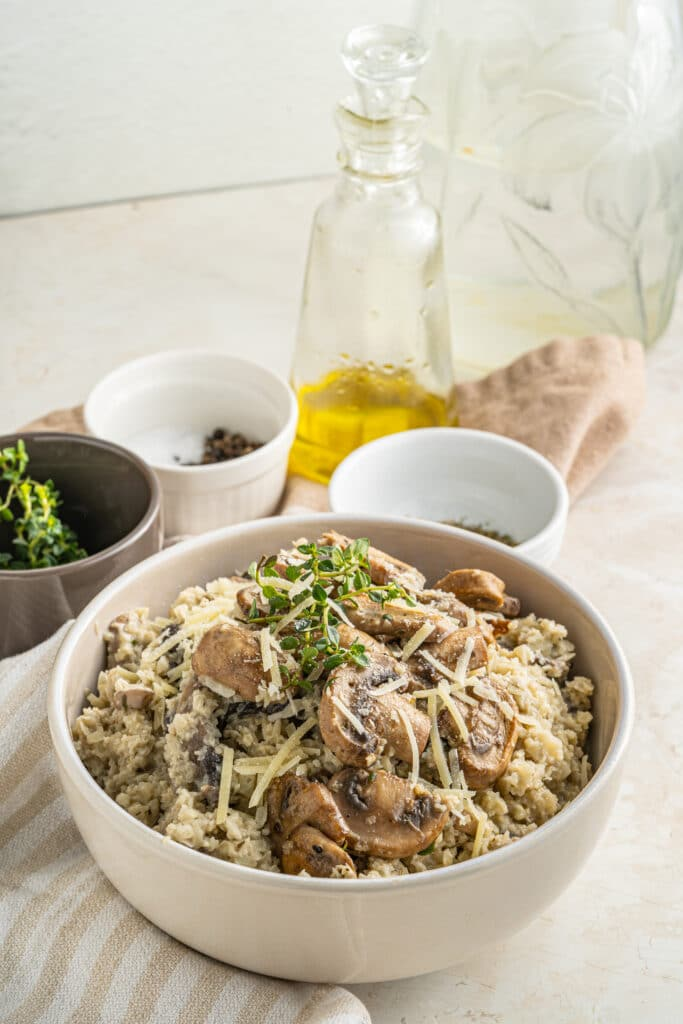 Picture of cauliflower rice risotto close up with mushrooms and shredded cheese on top with two small white jars of seasonings up top behind an olive oil jar and a brown bowl of green spices.