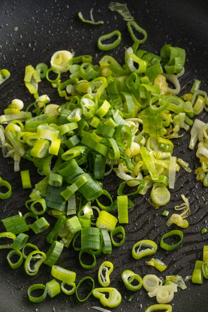 Picture of chopped green onions in a pan with olive oil.