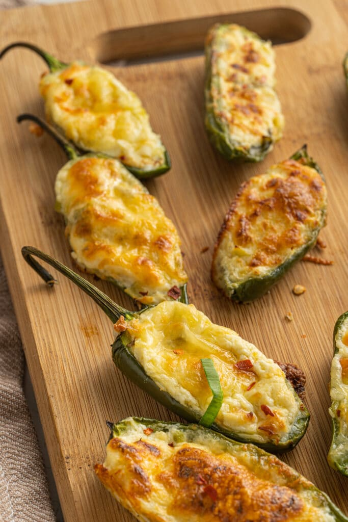 Cooked jalapeño poppers recipe with browned melted cheese on top on a wooden cutting board.