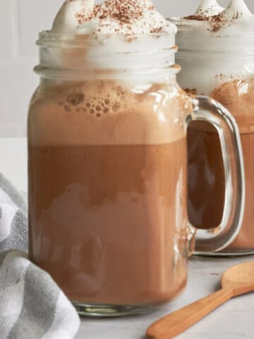 Close up of hot cocoa with whipped cream dripping on top of a clear mason jar mug with a wooden spoon in bottom right corner and a grey and white stripe towel in bottom left corner.