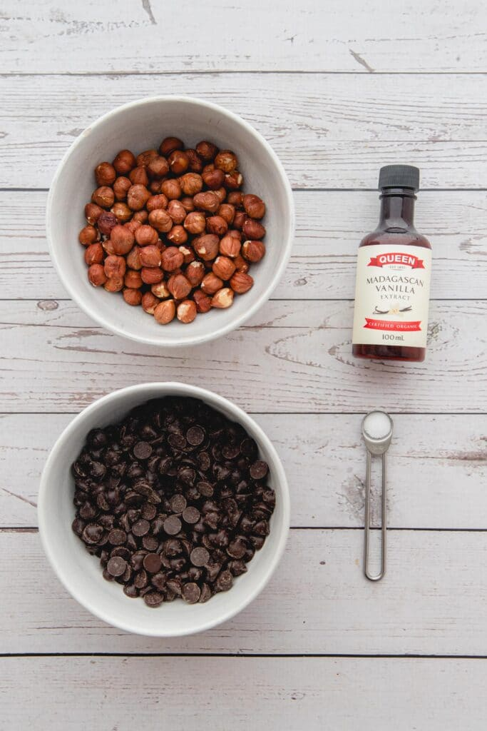Overhead picture of four ingredients on a white wood background, hazelnuts and chocolate chips in white bowls.