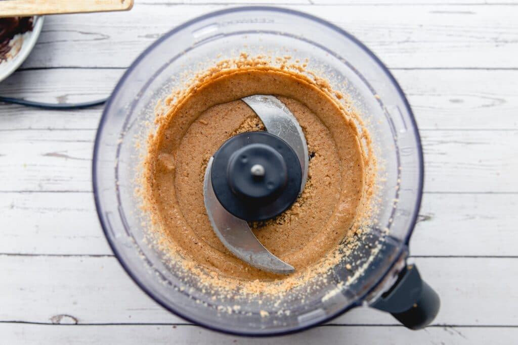 Overhead picture of blended hazelnuts in a food processor.