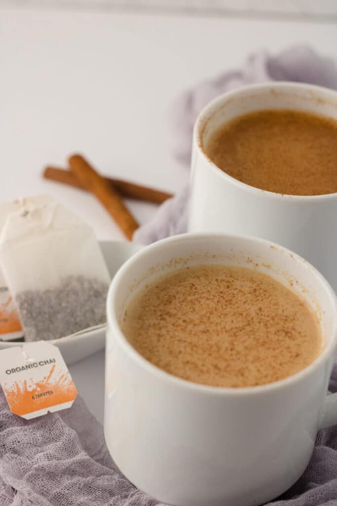 Picture of apple chai latte in a white mug on a grey cloth with tea bags in the corner and another white mug of latte in the back.