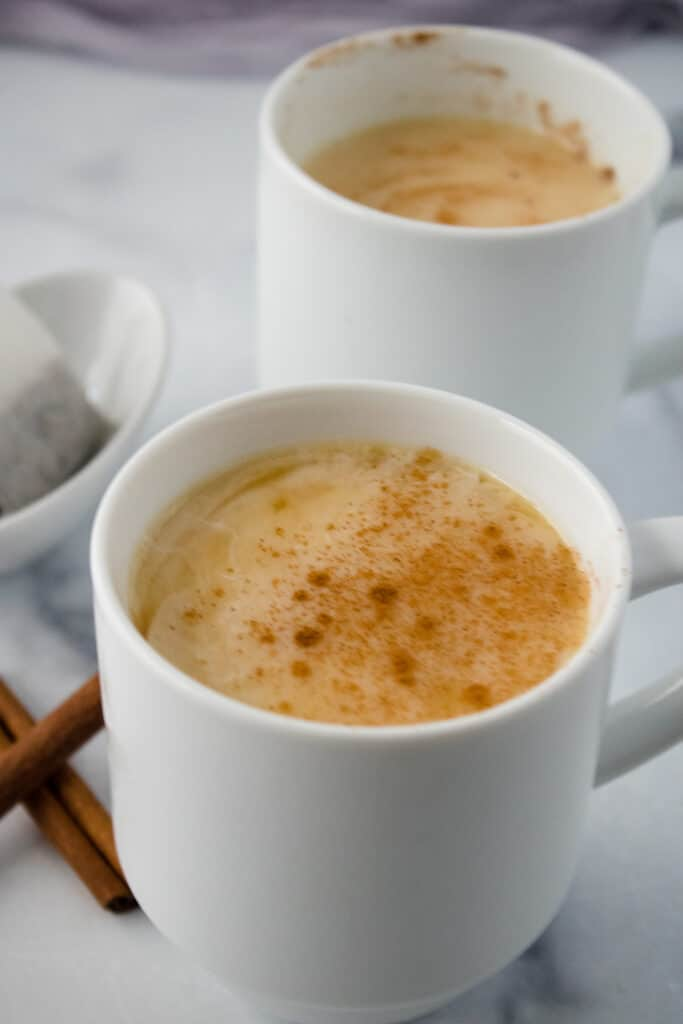 Picture of apple chai latte in a white mug on a grey cloth with tea bags in the upper left corner and another white mug of latte in the back.