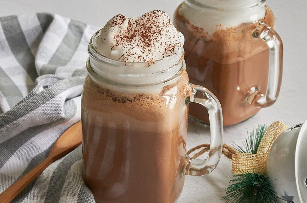 Horizontal picture of Two clear glass mason jar mugs with hot cocoa with whipped cream dripping on top with a wooden spoon on a grey and white striped towel in bottom left corner and a small piece of evergreen in the bottom right corner.
