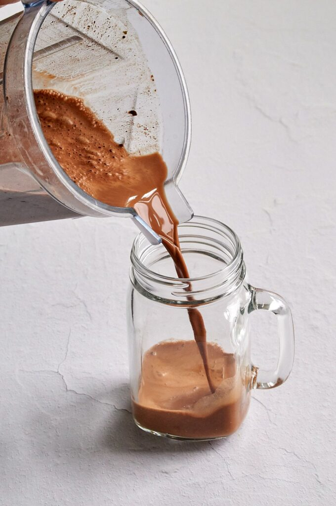 Picture of the hot chocolate being poured from a clear blender into a clear glass mason jar mug.